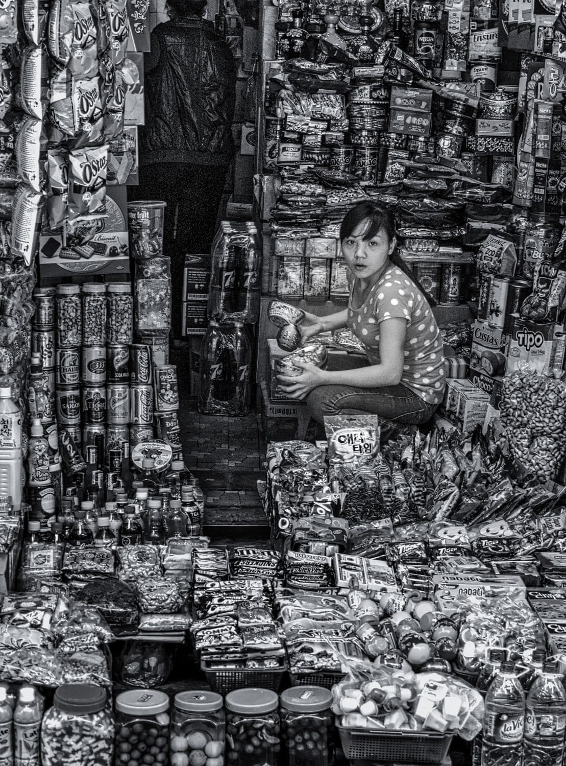 Black and white photo of woman squatting in store front in Vietname